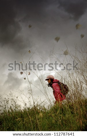 Young girl with hat and backpack walking alone in the countryside under bad weather