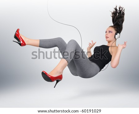 Young girl with headphones in unreal pose (concept)