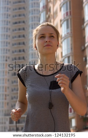young girl with headphones makes jog around the city, on the back of high buildings