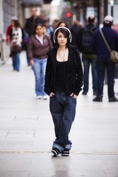 Young girl with headphones standing on sidewalk