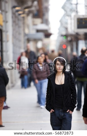 Young girl with headphones standing on sidewalk