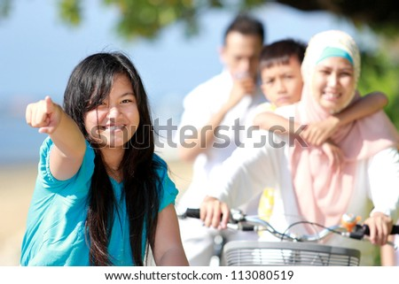young girl with her family riding bikes outdoor