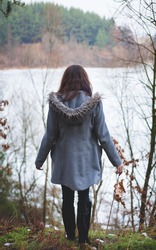 Young girl with her hair stands near the water in the cold season. Back view