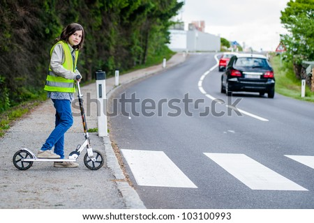 Young girl with her scooter will go on the crosswalk