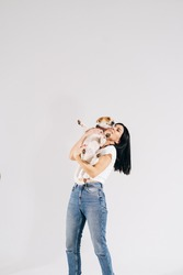 Young girl with his dog at studio. Young owner hugs his pet. young and beautiful girl holding her dog in her arms with love and playing with hem, against a white background