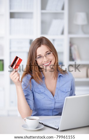 Young girl with laptop and credit card at home