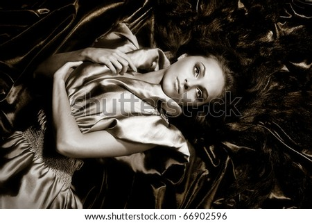 Young girl with long black hair lying poses no iridescent fabric - stock photo