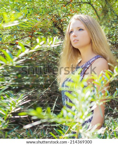 young girl with long blonde hair in a long Board is in among the bushes of sea-buckthorn in a Sunny bright day