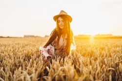 Young girl with long curly hairand freckles face, in hat, in light white dress with floral print, standing in wheat field, posing for camera, in background sundown