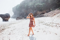 young girl with long hair in sunglasses and red dress with patterns posing on the beach of Bali Indonesia around the rock ocean and white sand stylish girl fashion lock