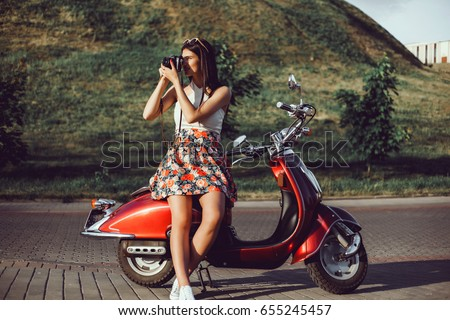 young girl with long hair in sunglasses in a black t-shirt tattoo on his shoulder in white pants with red lipstick posing on a retro scooter Vespa colors tiffany vintage style straw hat with a stylish
