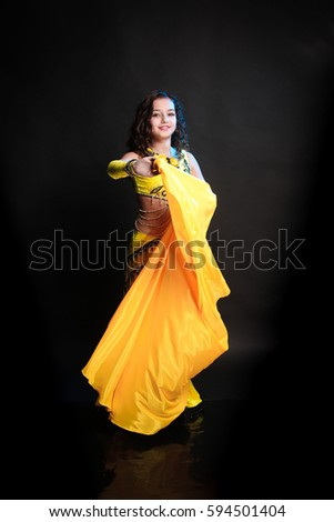 3b22e7d7d52 young girl with long hair in yellow dress with a shawl oriental dancer  posing and dancing