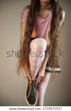 young girl with long hair straightens her white and pink stockings. Legs and sneakers close-up. Hair fixed ears fantastic animal. Cosplay, anime, fantasy, wig, sneakers