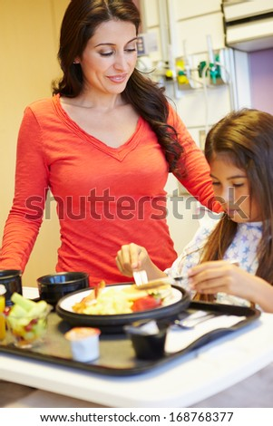 Young Girl With Mother Eating Lunch In Hospital Bed