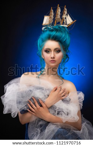 Young girl with naked shoulders and painted blue hair stowed in an artistic hairdo with a toy sailboat in her hair, covering her chest with blue and white veils. Black-blue background. Copy space #1121970716