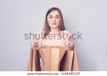 Young girl with packages purchases with amazement looks on you, portrait, toned