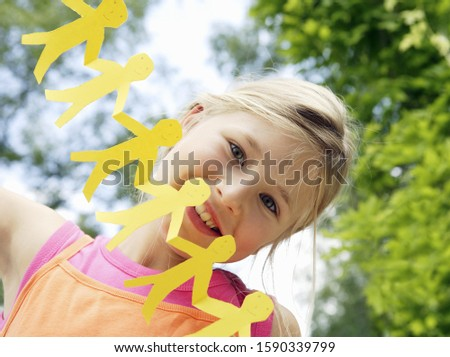 Young girl with paper cut-out people