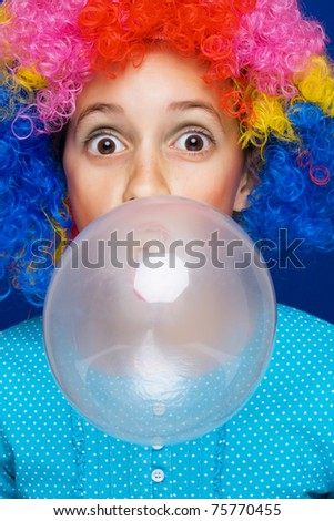 Young girl with party wig blowing bubble gum balloon