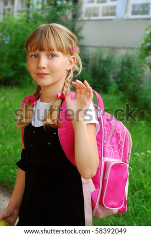 young girl with pink backpack going to school and waving hand to her parents