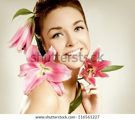 young girl with pink lily laughs