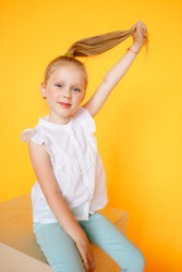 Young girl with plain pure sking and strong blonde fair hair. Hand on hairs. Little girl smiling in camera. Beautiful Studio portait of young child.