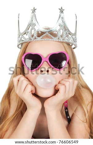 Young girl with princess crown and glasses are making a bubble from the gum over white