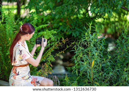 Young girl with red hair in a floral summer dress out in the garden taking photos with her camera