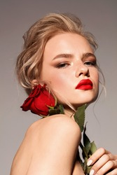 Young girl with red lips and rose. Blonde. Make up. Perfect style.