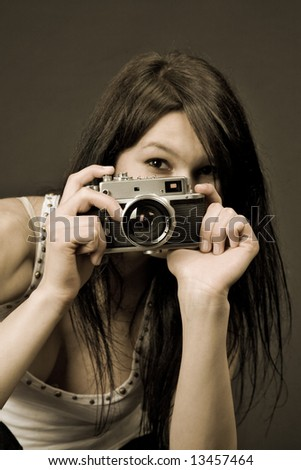 Young girl with retro camera, sepia old style