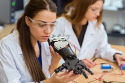 Young girl with serious facial expression holding and checking mechanical hand. Female scientist carefully examining mechanism, checking how everything working while her colleague working behind.