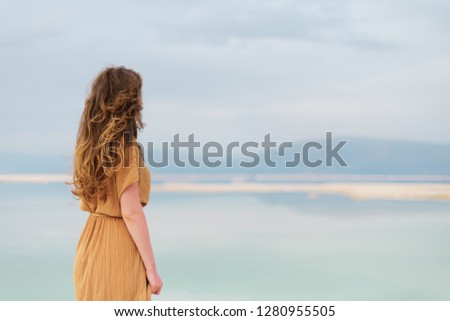 Young girl with shining blonde hair goes to seaside, Dead Sea beach. Banner. Travel, summer vacation, holiday, freedom concept. Digital detox. Sea background, copy space. #1280955505