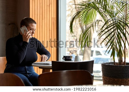 Young girl with short hair and nose piercing sits in a cafe. A woman is talking on the phone and work at a tablet. The concept of freelancing and remote work. ストックフォト ©