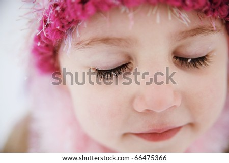 Young girl with snowflakes on long dark eyelashes wearing a hat outdoors in winter.
