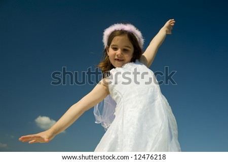 young girl with spreads arms against blue sky - stock photo