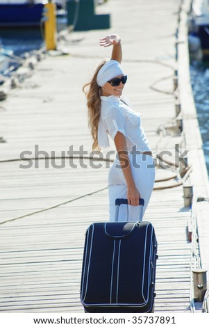 Young girl with suitcase going on voyage