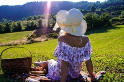 Young girl with the picnic basket on the grean meadow under the sun