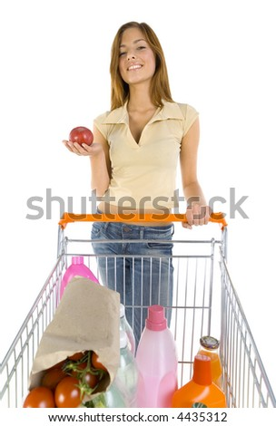 Young girl with trolley. Holding apple in hand. Smiling and looking at camera. White background, front view