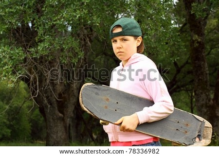 Young girl with well used scateboard