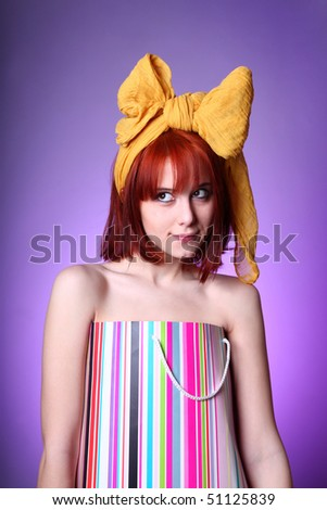 Young girl with yellow bow tie on head in present box at violet background.