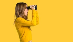 young girl with yellow sweater and looking in the distance with binoculars on isolated yellow background
