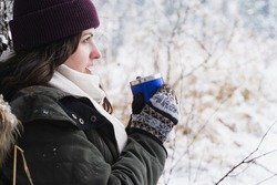 Young girl, woman in knitted mittens drinks tea, drinks coffee from thermo mug. Walking in beautiful winter forest covered with snow. Magnificent nature. Fashionable image, clothes, parka, hat, scarf.