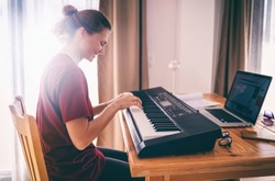 Young girl woman learns to sing and play the piano from a video conference from a laptop. Education video calls self education.