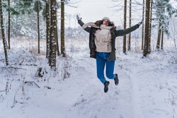 Young girl, woman walks is jumping in beautiful winter forest among trees, firs, covered with snow. Magnificent nature and views. Fashionable image, clothes, parka, hat, mittens, blue jeans.