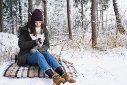 Young girl, woman with mobile phone. Walking in beautiful winter forest among trees, firs, covered with snow. Magnificent nature and views. Fashionable image, clothes, parka, hat, mittens, blue jeans.