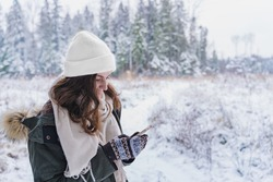 Young girl, woman with mobile phone walks in beautiful winter forest among trees, firs, covered with snow. Magnificent nature and views. Fashionable image, clothes, parka, hat, mittens, blue jeans.