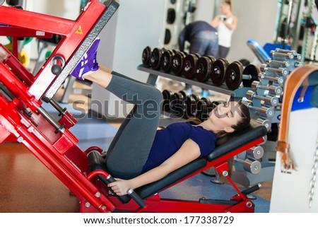 Young girl works out on training apparatus inside in fitness center