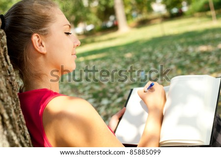 young girl writer in park, writing book