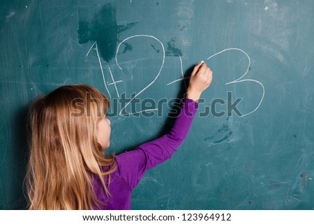 Young girl writing numbers on chalkboard with chalk