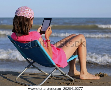 young girls arrives on the sea beach reads an e-book  Photo stock ©
