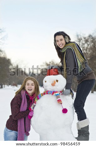 Young girls building a snowman